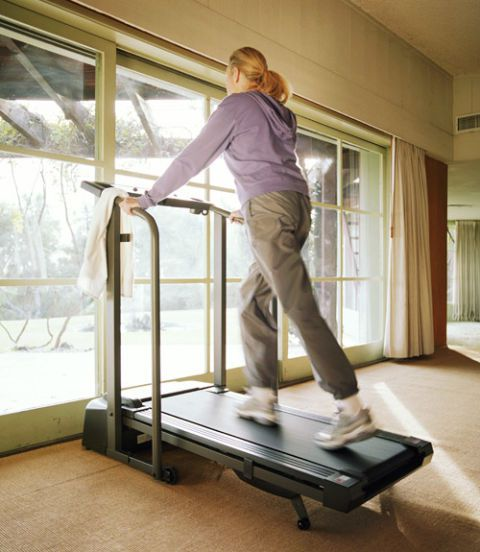 γυναίκα walking on a treadmill at home