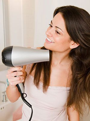אִשָׁה blow drying her hair