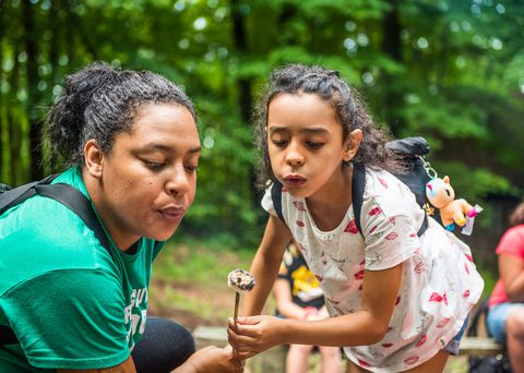 ΕΝΑ Girl Scout of the USA and her troop leader blow on a roasted marshmallow at a campout.