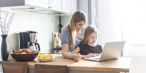 मां and daughter using laptop in kitchen